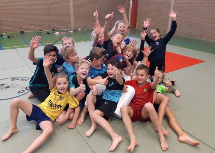 Groep kinderen zit juichend in de sporthal