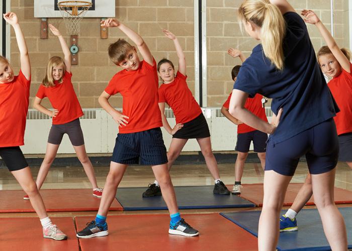 Kinderen doen rek-en strekoefeningen in de gymzaal